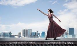 Blind kvinna i lång röd klänning överst av byggnad Blandat massmedia royaltyfri foto