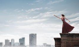 Blind kvinna i lång röd klänning överst av byggnad Blandat massmedia arkivfoton