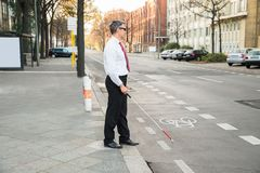 Blind man crossing road Royalty Free Stock Image