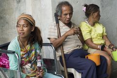 Blind Man beside disabled Beggar at Church Portal are familiar scenes found in public places. San Pablo City, Laguna, Philippines – January 9, 2016: Blind Man Royalty Free Stock Image