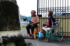 Blind Man beside disabled Beggar in wheelchair at Church yard Gate Portal to seek alms. San Pablo City, Laguna, Philippines - October 20, 2016: Blind Man beside Stock Photos