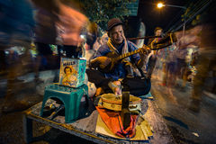 Blind man plays multiple instruments for donations on street at night market Royalty Free Stock Photos