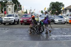 Blind man pushing wheelchair of disabled beggar. San Pablo City, Laguna, Philippines - December 3, 2016: Blind man pushing wheelchair of disabled beggar Royalty Free Stock Images