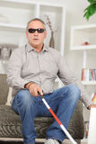 Blind man sitting on couch Stock Images