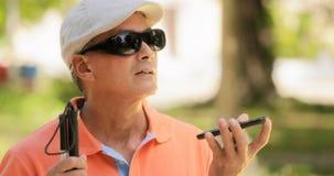 Blind man som talar med tala för man för mobiltelefon rörelsehindrat royaltyfri bild