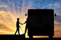 Blind man with to cane helping get on bus sunset Royalty Free Stock Photos
