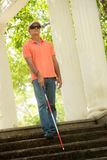 Blind Man Walking And Descending Stairs In City Park. Hispanic blind man, latino people with disability, handicapped person and everyday life. Visually impaired Stock Photos