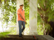 Blind Man Walking And Descending Steps In City Park. Hispanic blind man, latino people with disability, handicapped person and everyday life. Visually impaired Stock Photo