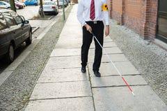 Blind man walking on sidewalk. Holding Stick Wearing Armband Stock Images