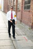 Blind man walking on sidewalk holding stick Royalty Free Stock Photos