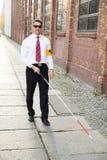 Blind man walking on sidewalk holding stick. Wearing Armband Royalty Free Stock Photos