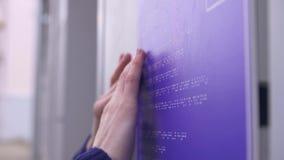 Blind meisje op de straat die een braille-doopvont op een de bouw teken lezen stock video