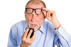 Blind old man. Closeup portrait, senior mature man, nerd black glasses, having trouble seeing cell phone screen because of vision problems. Bad text message royalty free stock photography