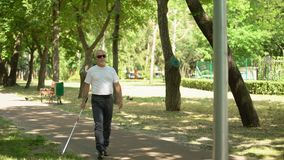 Blind old man detecting obstacles with white cane, bumping into pillar in park