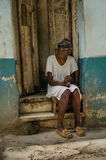 Blind old woman sits on steps in front of her home in Havana Stock Photography