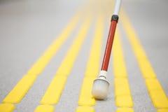 Blind pedestrian walking on tactile paving Royalty Free Stock Photos