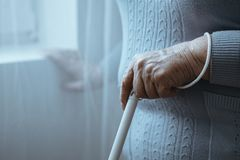 Blind person holding white cane royalty free stock image