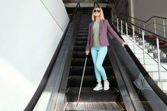 Blind person med den l?nga rottingen p? rulltrappan arkivbild