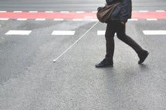 Blind person som går med en pinne som korsar en fot- gångbana tomt kopieringsutrymme Fotografering för Bildbyråer