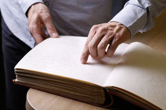 Blind person touching book, written in braille writing Royalty Free Stock Images