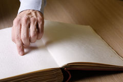 Blind person touching book, written in braille writing Royalty Free Stock Photo