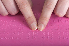 Blind reading pink text. Blind reading text in braille language Royalty Free Stock Photos