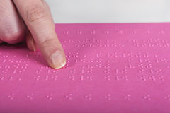 Blind reading pink text. Blind reading text in braille language royalty free stock image