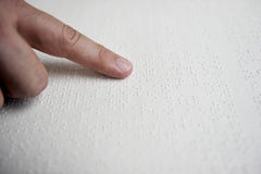 Blind reading text in braille language Stock Photo