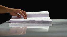 Blind reading text in braille language. Black background. Side view. Braille blind reading text on a white page. Black background. Side view stock footage