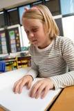 Blind schoolmeisje die een braille-boek in het klaslokaal lezen royalty-vrije stock foto