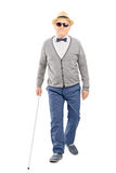 Blind senior gentleman walking with a stick Stock Image