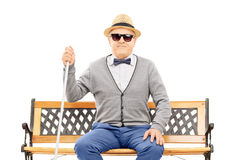 Blind senior man seated on bench isolated on white Stock Photos