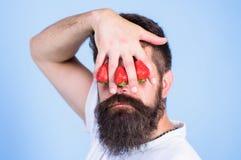 Blind van aardbei De greephand van mensen gebaarde hipster met aardbeien voor ogen Blik van de mens door bessen wordt geblokkeerd stock afbeeldingen