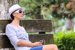 Blind woman with cellphone in park Stock Image