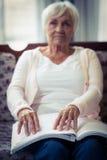 Blinde Frau, die ein Blindenschrift-Buch liest Stockbilder