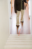 Blinde Frau, die einen Spazierstock auf Treppenhaus verwendet Lizenzfreie Stockfotos