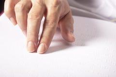 Blinde Frau las das Buch, das in Blindenschrift geschrieben wurde Schließen Sie herauf Fingernote zu Blindenschrift-Code Stockfotos