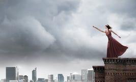 Blinde in lange rode kleding boven de bouw Gemengde media royalty-vrije stock fotografie