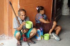 Blinde oude mannelijke bedelaar en vrouwenescorte die aalmoes zoeken bij kerk poortruïnes stock foto