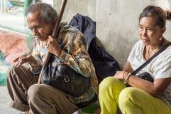 Blinde oude mannelijke bedelaar en vrouwenescorte die aalmoes zoeken bij kerk poortruïnes stock foto's