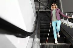 Blinde persoon met lang riet op roltrap royalty-vrije stock afbeeldingen