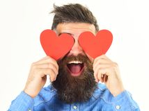 Blinded by love concept. Man with beard holds red hearts stock photo