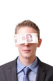 Blinded by the money. A smiling businessman blindfolded by a 500 mexican pesos note Royalty Free Stock Photos