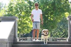 Blindenhund, der jungem Blinder hilft Stockfotografie