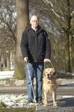 Blindenhund hilft einem blinden Mann Stockfoto