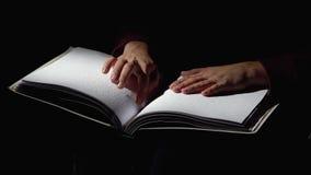Blindenschrift lesend, lernt der Mann, Blindenschrift im dunklen Studio zu lesen Abschluss oben stock video footage
