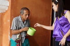 Blinder alter männlicher Bettler, der den Wasserschöpflöffel empfängt Almosen von einer Frau an den Kirchenportalruinen hält Stockfoto