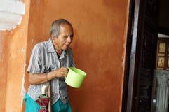 Blinder alter männlicher Bettler, der suchende Almosen des Wasserschöpflöffels an den Kirchenportalruinen hält Lizenzfreie Stockbilder