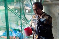 Blinder alter männlicher Bettler, der suchende Almosen des Wasserschöpflöffels an den Kirchenportalruinen hält Stockfoto