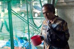 Blinder alter männlicher Bettler, der suchende Almosen des Wasserschöpflöffels an den Kirchenportalruinen hält Stockbild